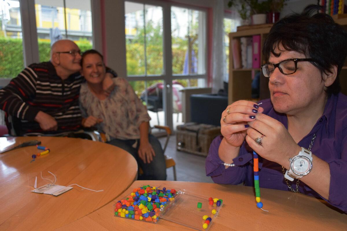 Während Jutta Sprenger in das Auffädeln von Perlen für ein neues Armband vertieft ist, umarmt Günther Lanz die Mitarbeiterin Susanne Ledermüller impulsiv (im Hintergrund).