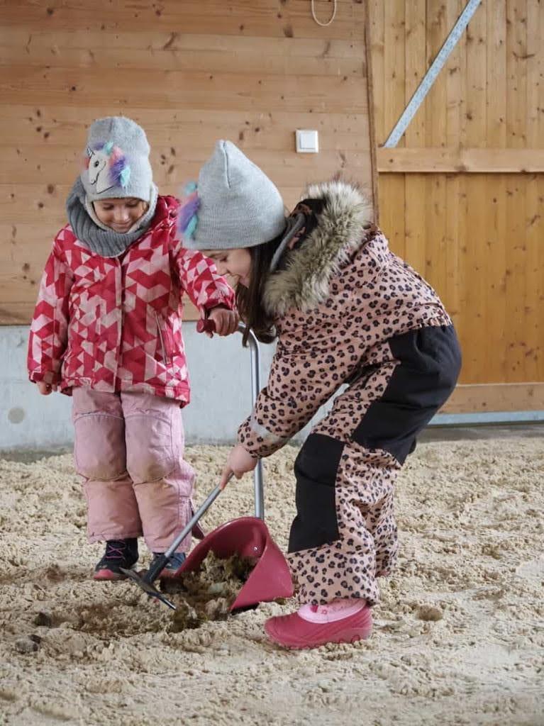 Verantwortung und Fürsorge: Für die beiden Mini-Pferde übernehmen die beiden Mädchen gern auch unliebsame Aufgaben ... und haben sichtlich Freude daran.