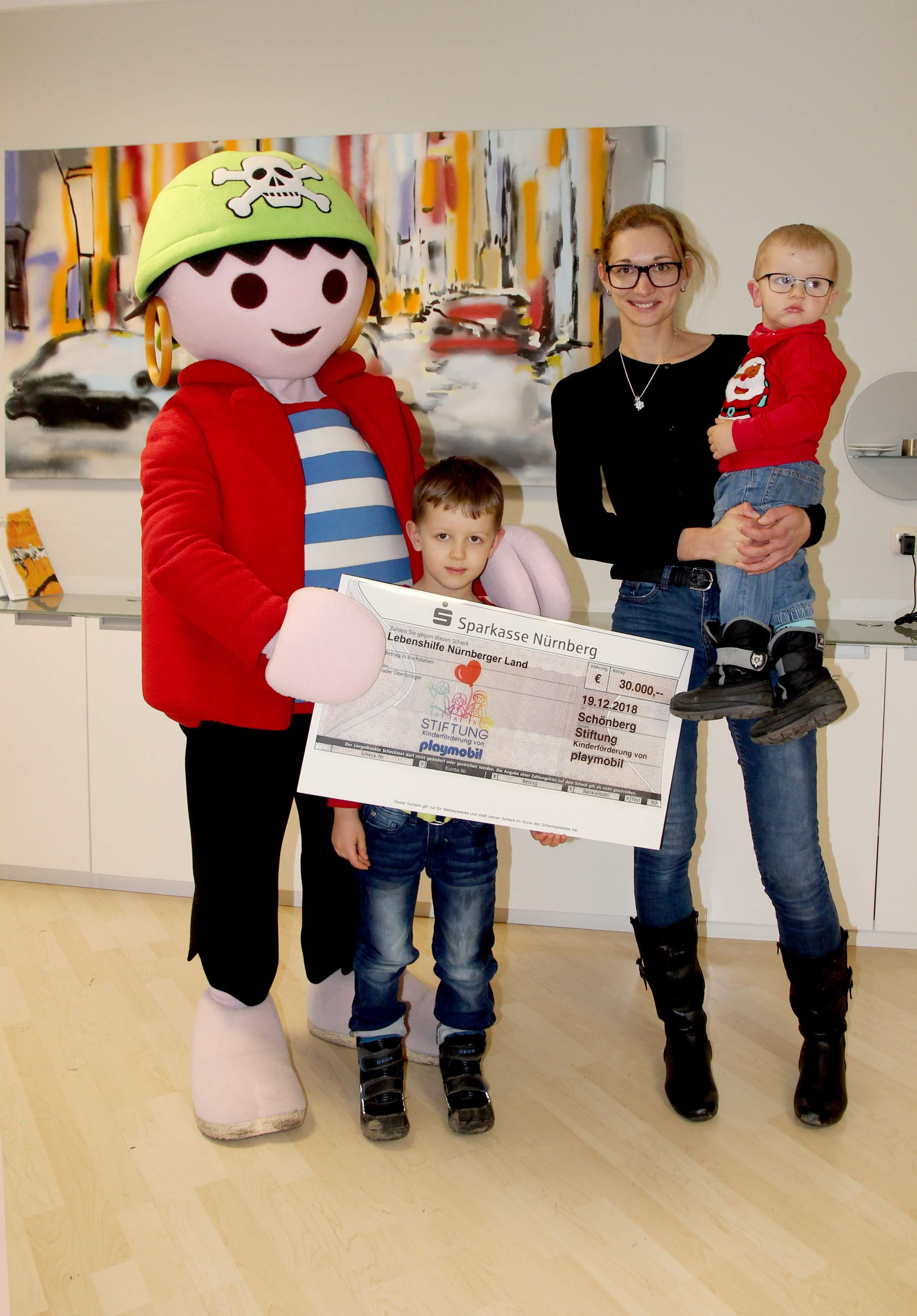 Playmobil-Maskottchen Rico überreichte die Riesenspende der Kinderstiftung. Stellvertretend für die Lebenshilfe Nürnberger Land nahmen die Frühförderkinder Emil und Marc die Spende entgegen.