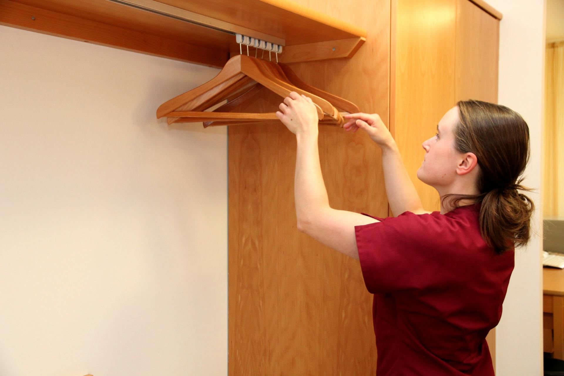 """""""Alle Kleiderbügel der Garderobe müssen in eine Richtung zeigen"""", sagt Michaela Dressel, die bei ihrer Arbeit viele Details beachten muss. Eine Herausforderung für die Frau mit Lernbehinderung."""