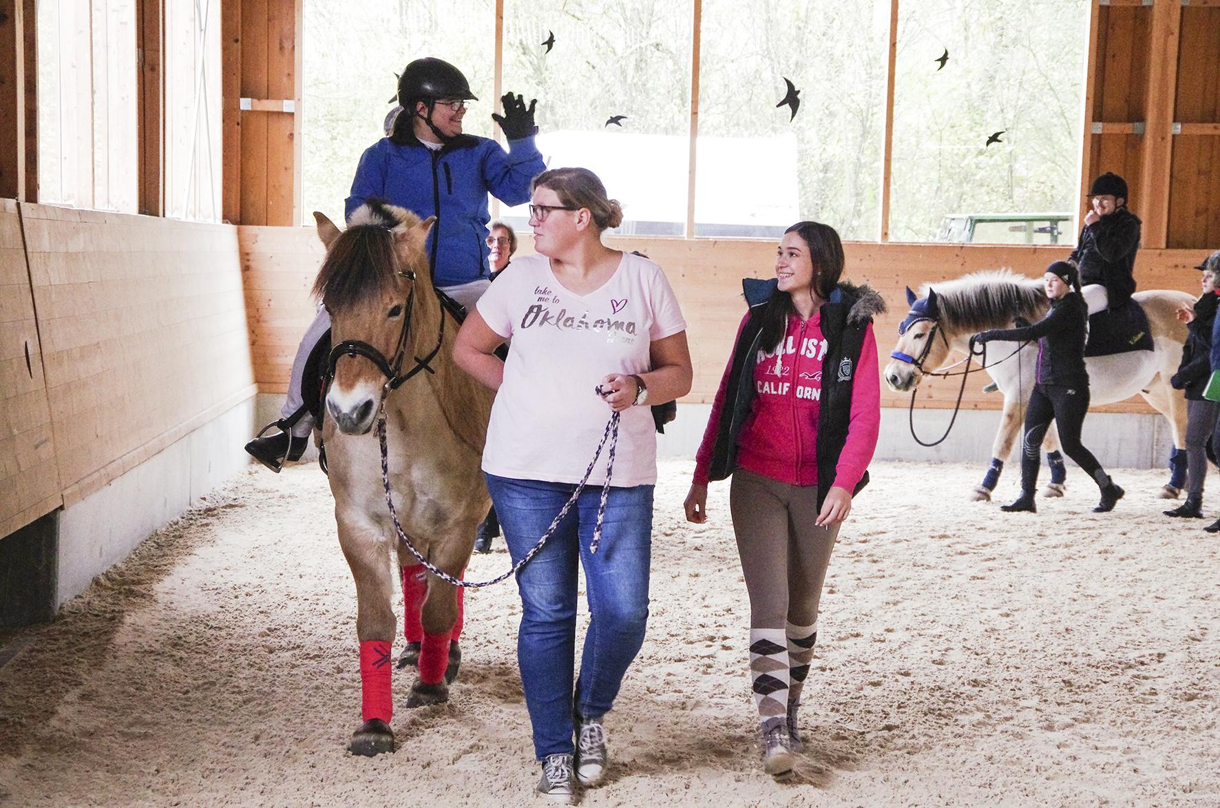 """Azubi Alina (rechts) unterstützt vom Boden aus Jessica, die dem Auftritt bei """"Faszination Pferd"""" gespannt entgegenblickt."""