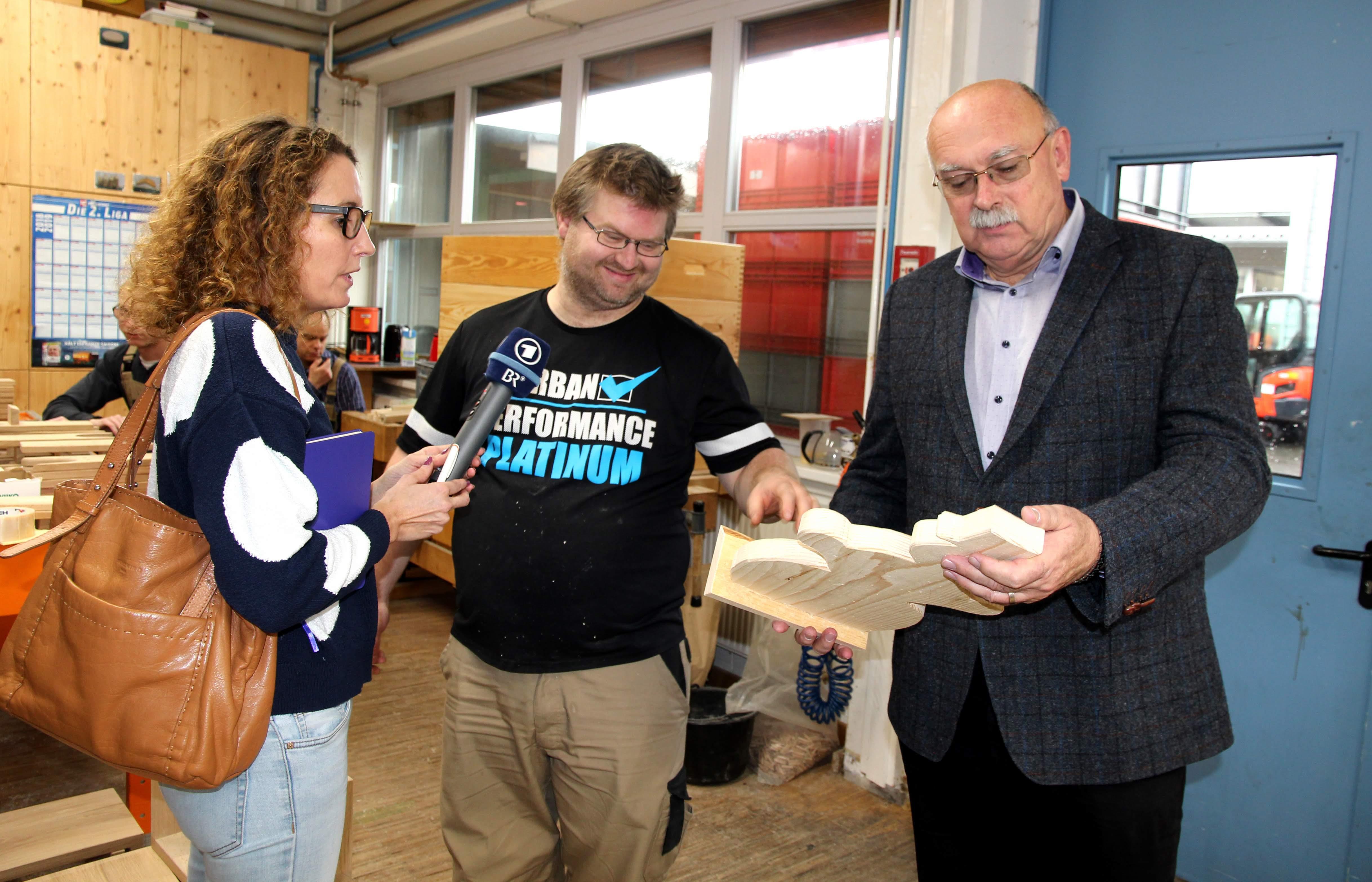 Anerkennender Blick: Werkstattleiter Hans-Manfred Wolf (rechts) mit BR-Redakteurin Christine Weirauch und Schreinerei-Mitarbeiter Thomas Amm.