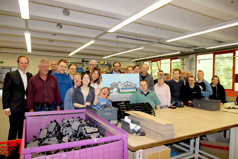 EuWe in Acryl: EuWe-Geschäftsführer Matthias Wexler (Bildmitte) und die Abteilungsleiter Peter Danner und Robert Eckert nehmen starke Eindrücke von ihrem Informationsbesuch in den Moritzberg-Werkstätten (hier in der Fertigungsgruppe 3, die insbesondere mi