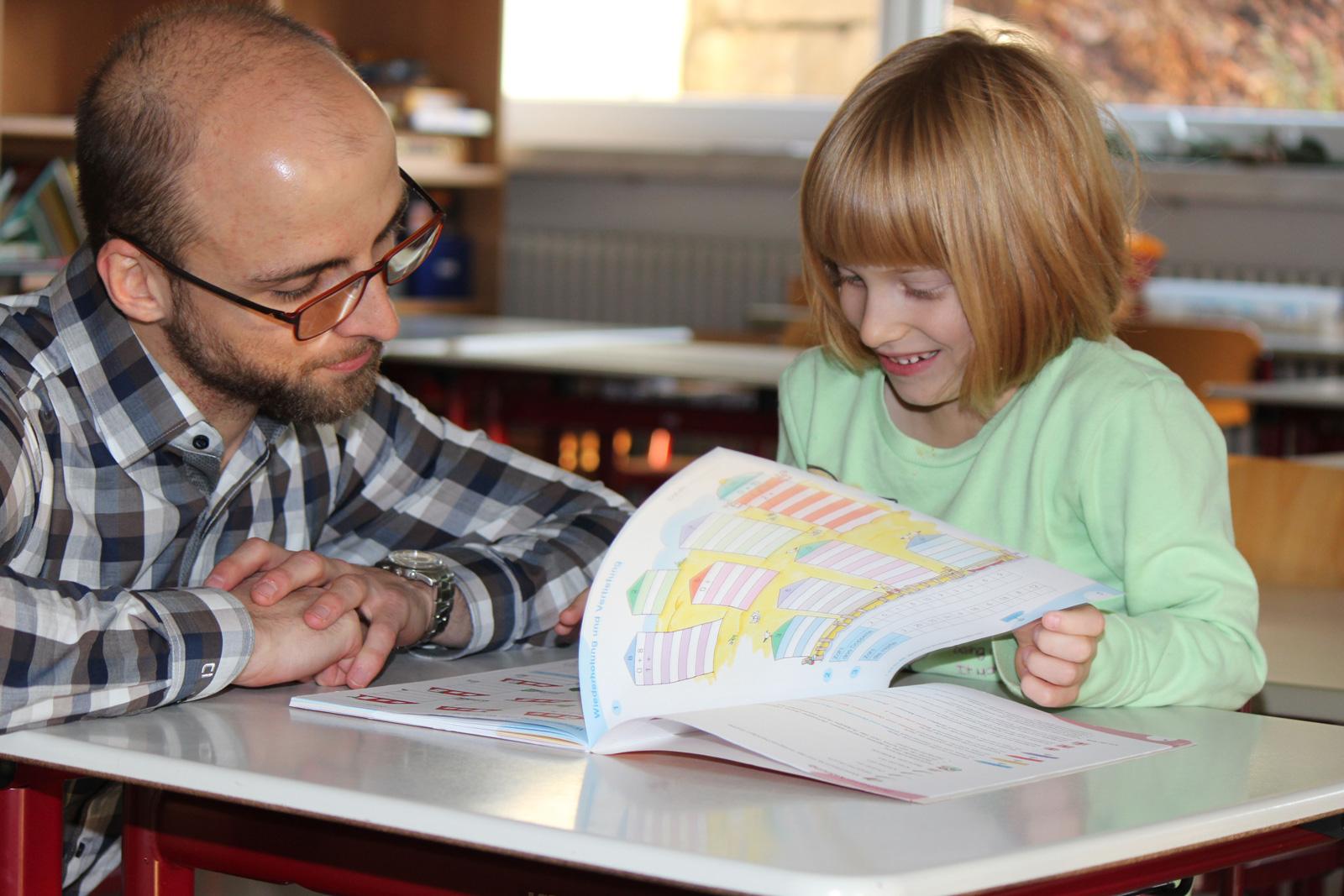"""Stärken stärken – das bringt Erfolg, weiß Schulstarthelfer Philip Minkenberg. Hier unterstützt er die sechsjährige Jolena und zeigt ihr, wie sie mit kleinen Übungseinheiten, ihre Aufgaben schaffen kann. """"Wir haben zusehends bemerkt, dass für Kinder der Ü"""