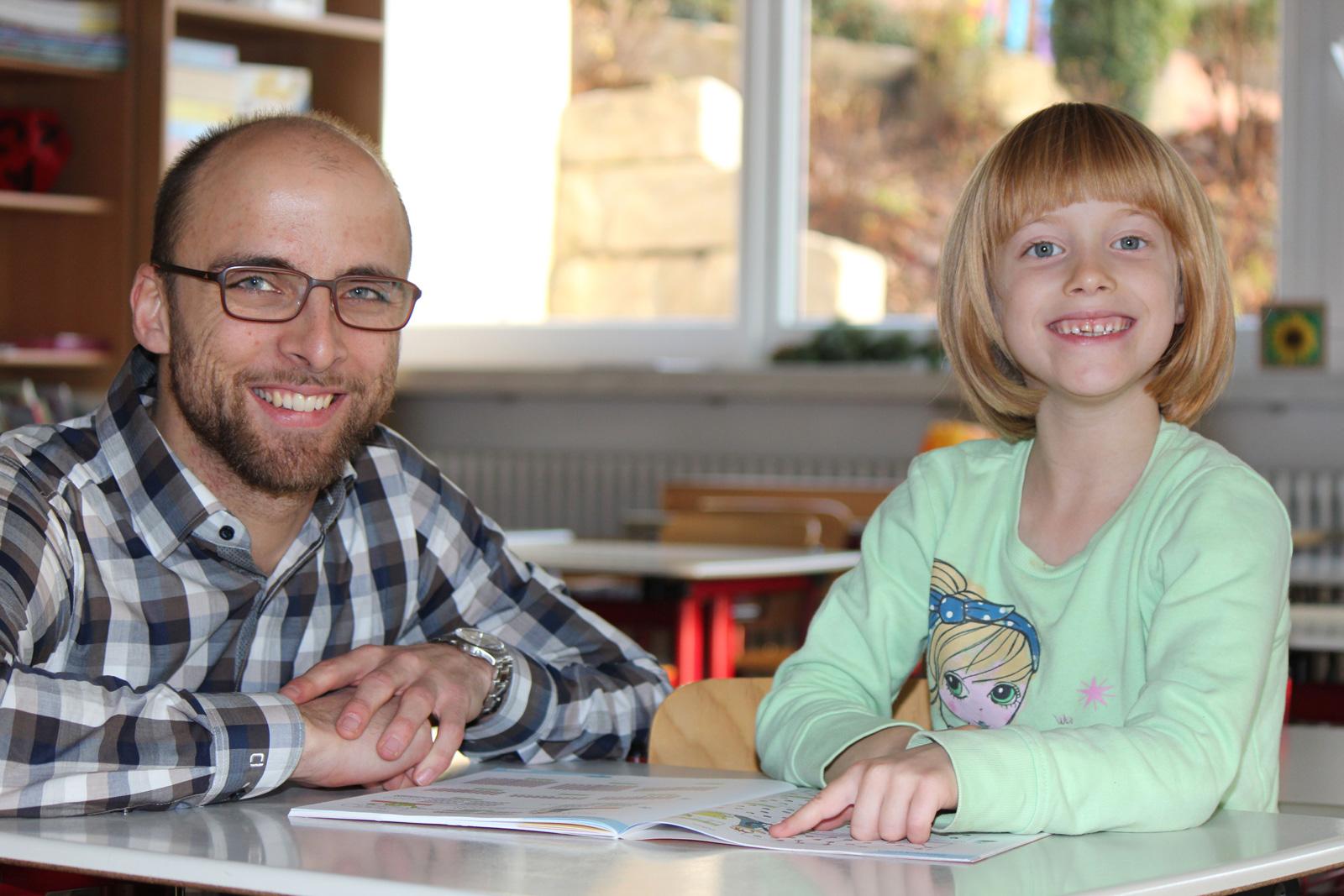 """Stärken stärken – das bringt Erfolg, weiß Schulstarthelfer Philip Minkenberg. Hier unterstützt er die sechsjährige Jolena und zeigt ihr, wie sie mit kleinen Übungseinheiten, ihre Aufgaben schaffen kann. """"Wir haben zusehends bemerkt, dass für Kinder der Üb"""