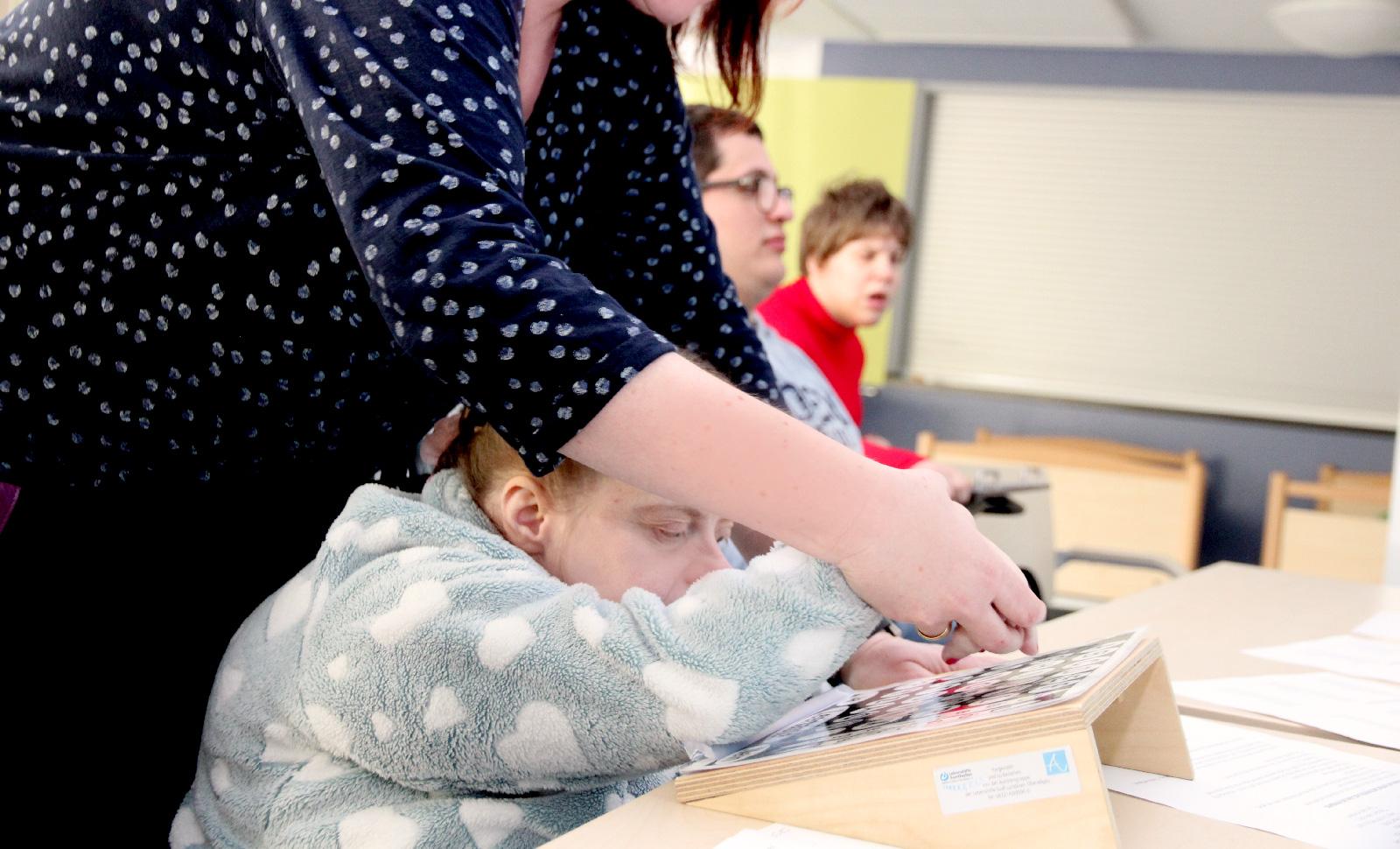 Gestützte Kommunikation, hier mit einer sog. Schreibtafel und eines Begleiters, ermöglicht es Menschen mit mehrfacher Behinderung zu kommunizieren.