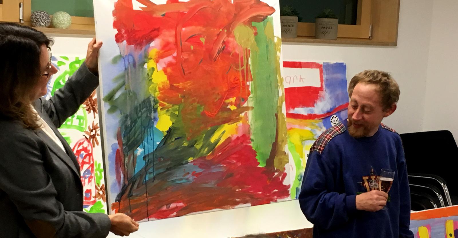 Farbenfrohe Stimmung: Malworkshop-Teilnehmer Christian Eibert präsentiert mit Kursleiterin Tanja Hoffmann stolz sein Kunstwerk.
