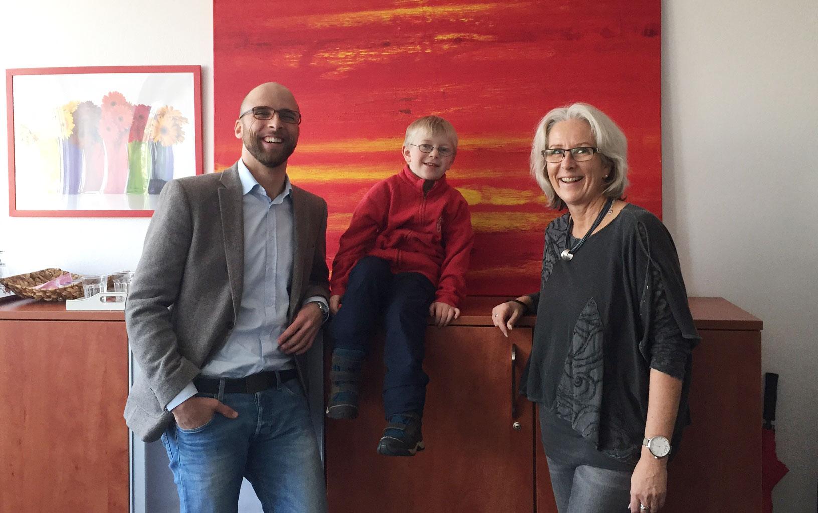 Schulcoach Minkenberg und Schüler Max Auer freuen sich, dass Max' Action Painting aus der Frühförder-Malterapie, so gut bei Schulleiterin Carola Stöhr ankommt.