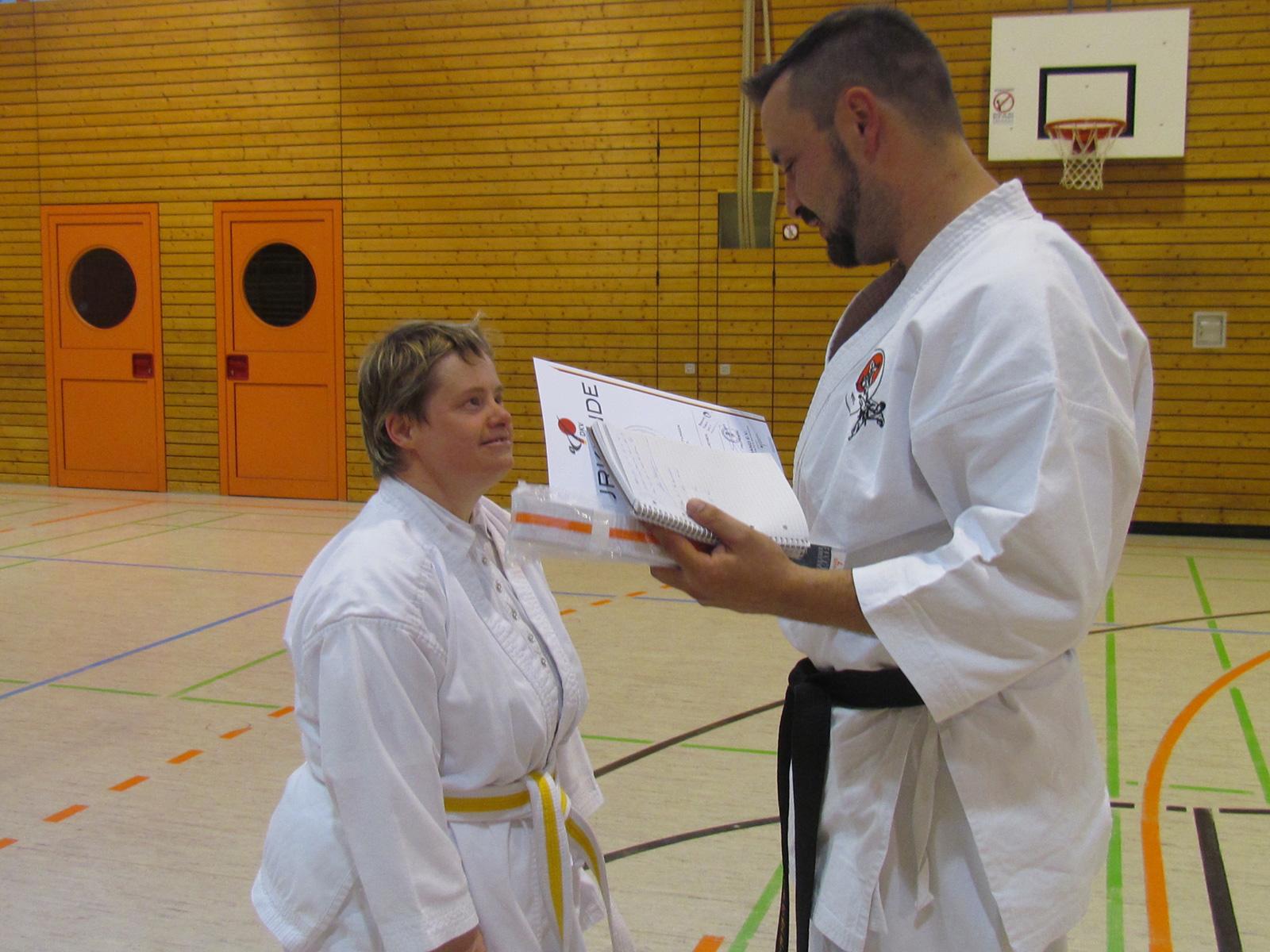 Heike Neumann nimmt stolz die Urkunde nach der erfolgreichen Gürtelprüfung entgegen.
