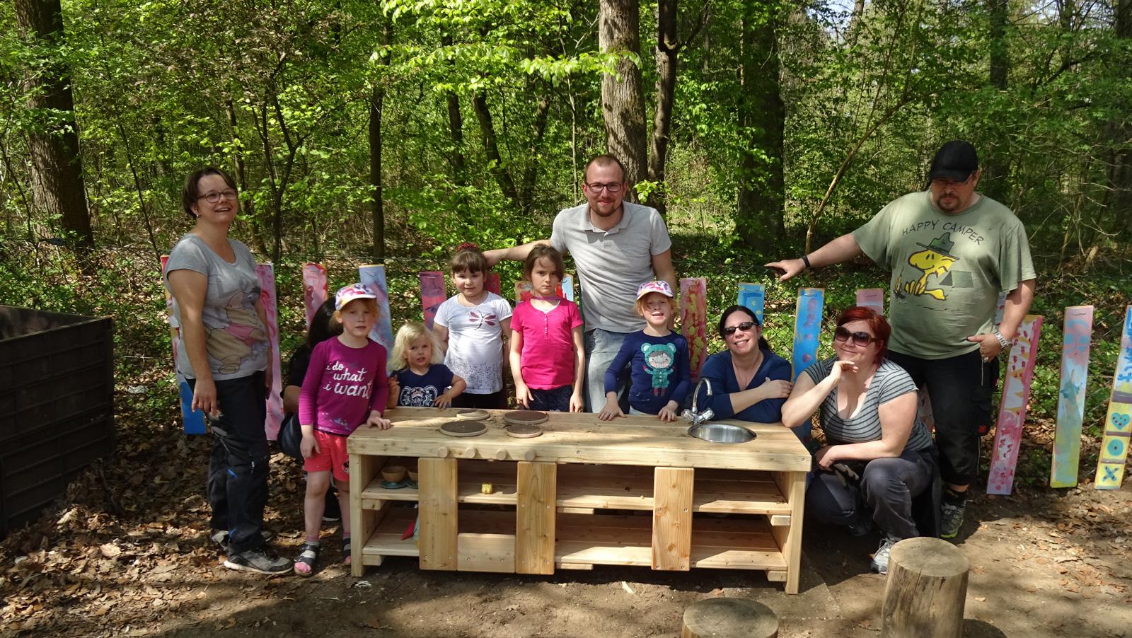 Das Foto zeigt einige der fleißigen Helfer mit Familie Kliegel vor der neuen Gartenspielküche.