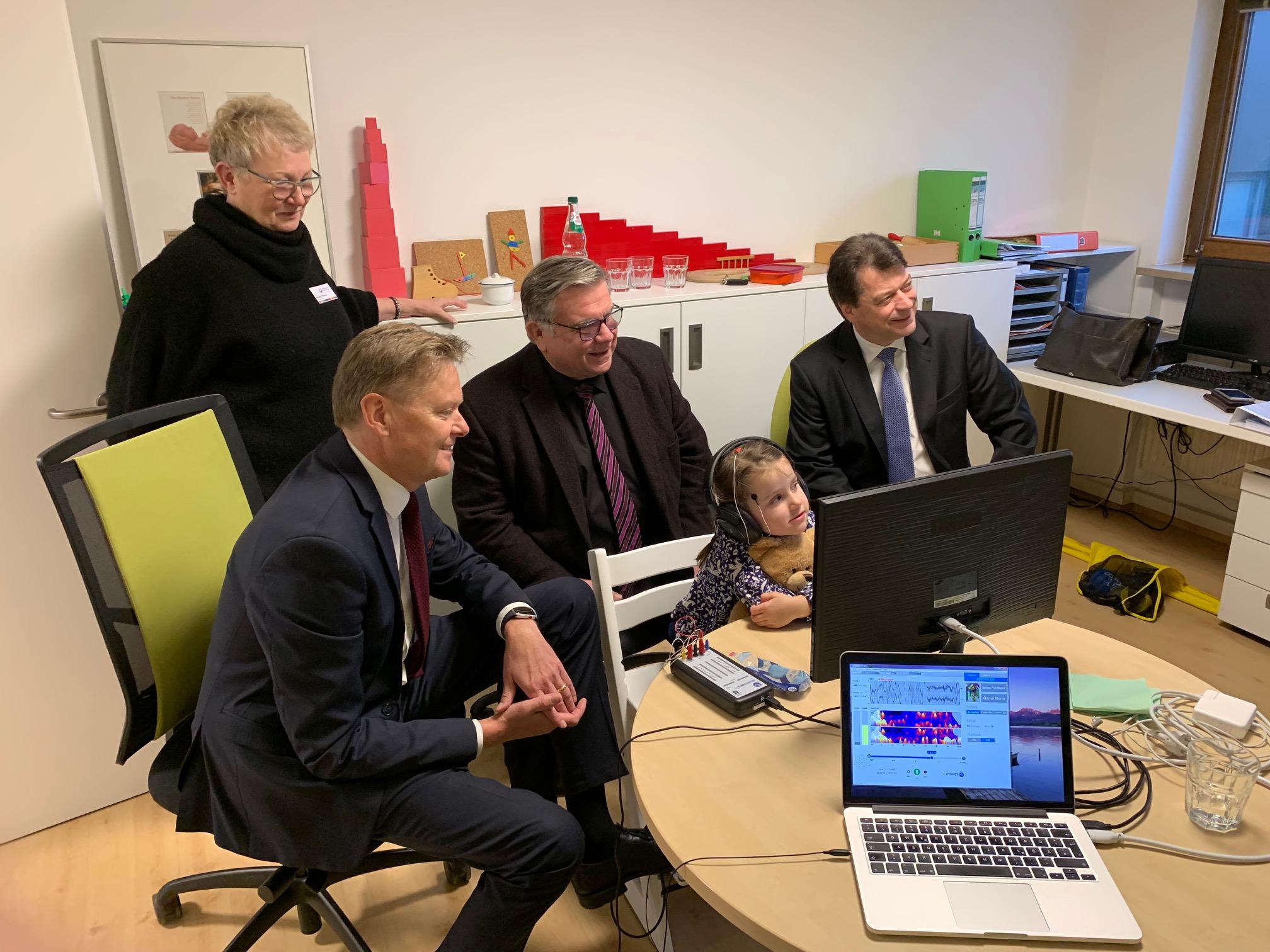 Neurofeedback-Therapie: Sparkassendirektor Matthias Benk (rechts) ist angetan von der Verwendung seiner Geburtstagsspende, die Renate Thoma und Frühförderkind Luci anschaulich demonstrieren.