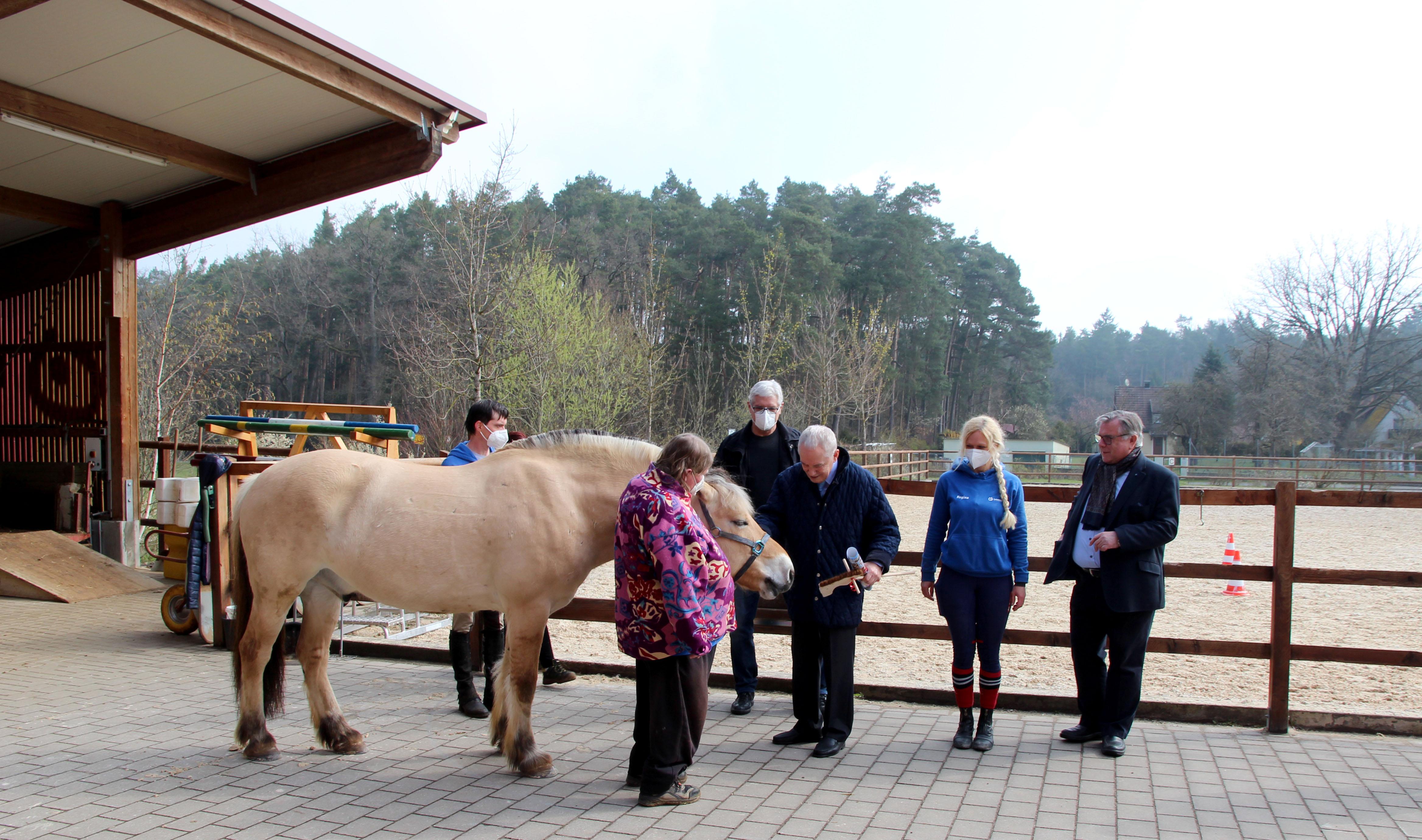 Pferdefreund Hans-Peter Schmidt mit Ivaldi und Iris Hoffmann. Die inklusive Mitarbeiterin übernimmt viele Tätigkeiten rund ums Füttern und Tier- und Stallpflege.