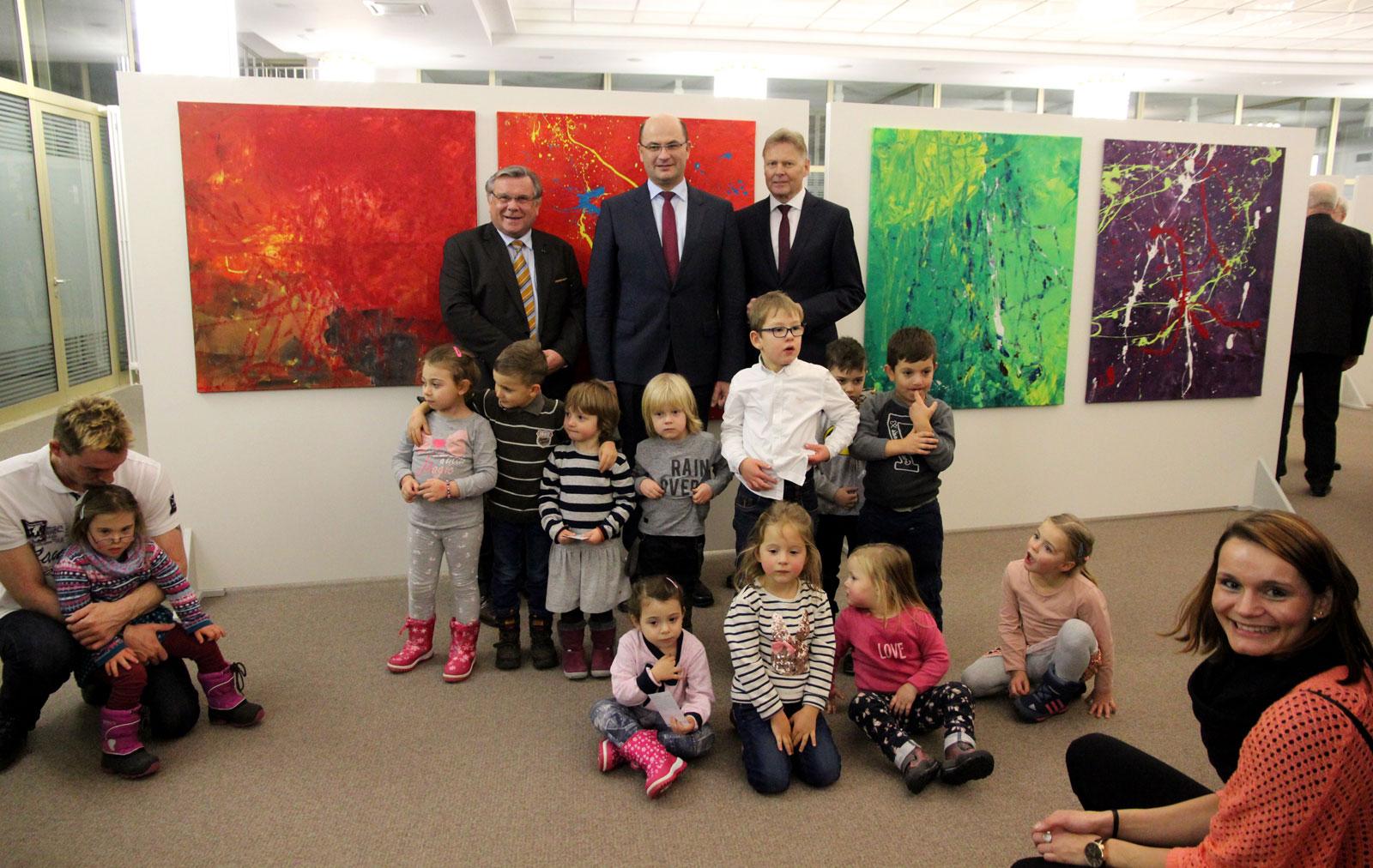 """Kita-Kinder, Staatssekretär Füracker sowie Gerhard John und Norbert Dünkel von der Lebenshilfe, geben den Startschuss für die Ausstellung """"20 Jahre Action Painting""""."""